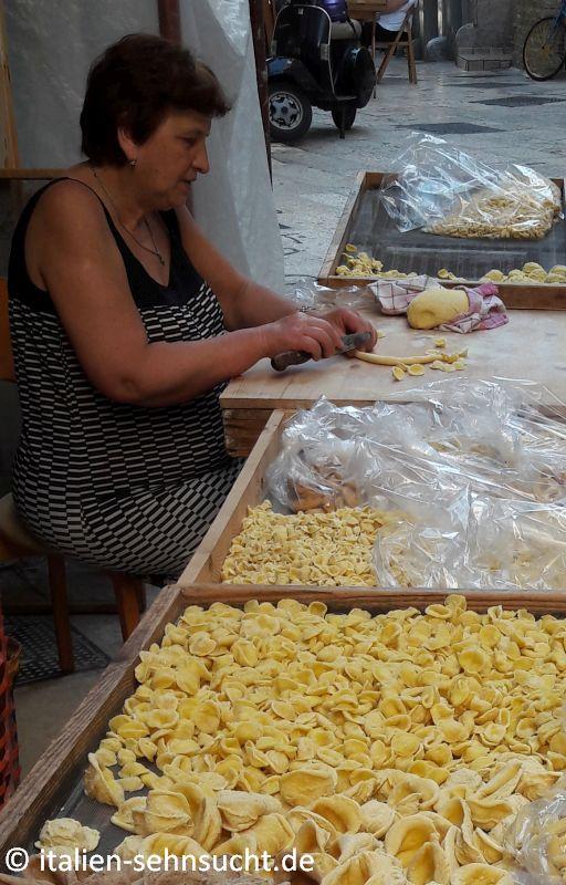 Eine ältere Dame im ärmellosen Sommerkleid stellt die Nudelspezialität Orecchiette her. Auf den Gittern neben ihr trocknet noch schon jede Menge fertige Pasta in der Sonne.