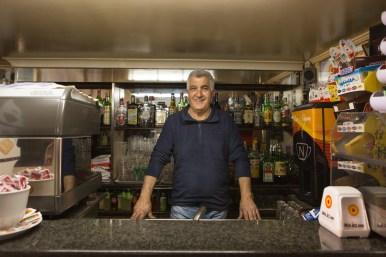 """Antonio, 52 anni, da 40 anni lavora al """"Bar Gervasi"""" nella piazza principale di Riace. Come molti riacesi vede in maniera positiva l'arrivo dei migranti nel suo paese."""