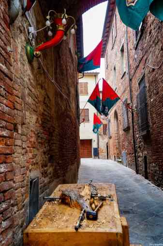 I suggestivi vicoli di Torrita di Siena con le bandiere delle contrade
