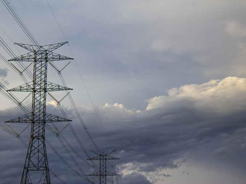 tall electricity transmission towers under cloudy sky