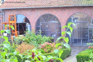 You can see the brewhouse and the kettles through the courtyard plants.