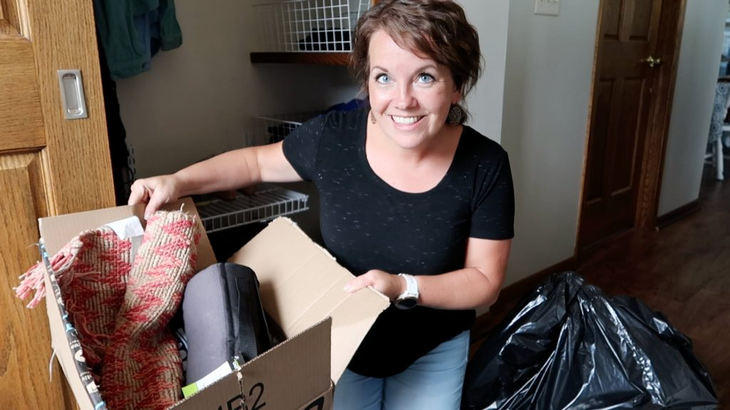 The minimal mom holding donation box next to a trash bag while decluttering