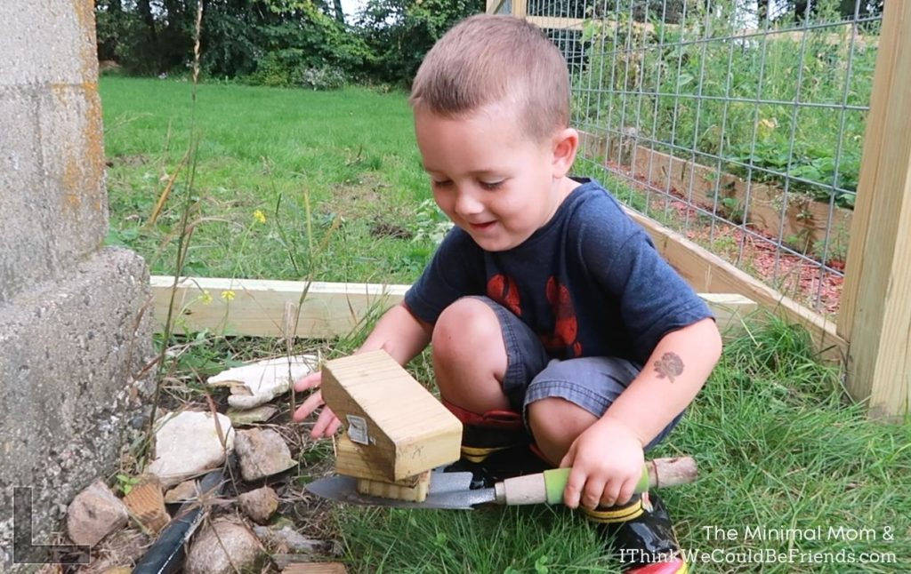 boy playing with wood and stones