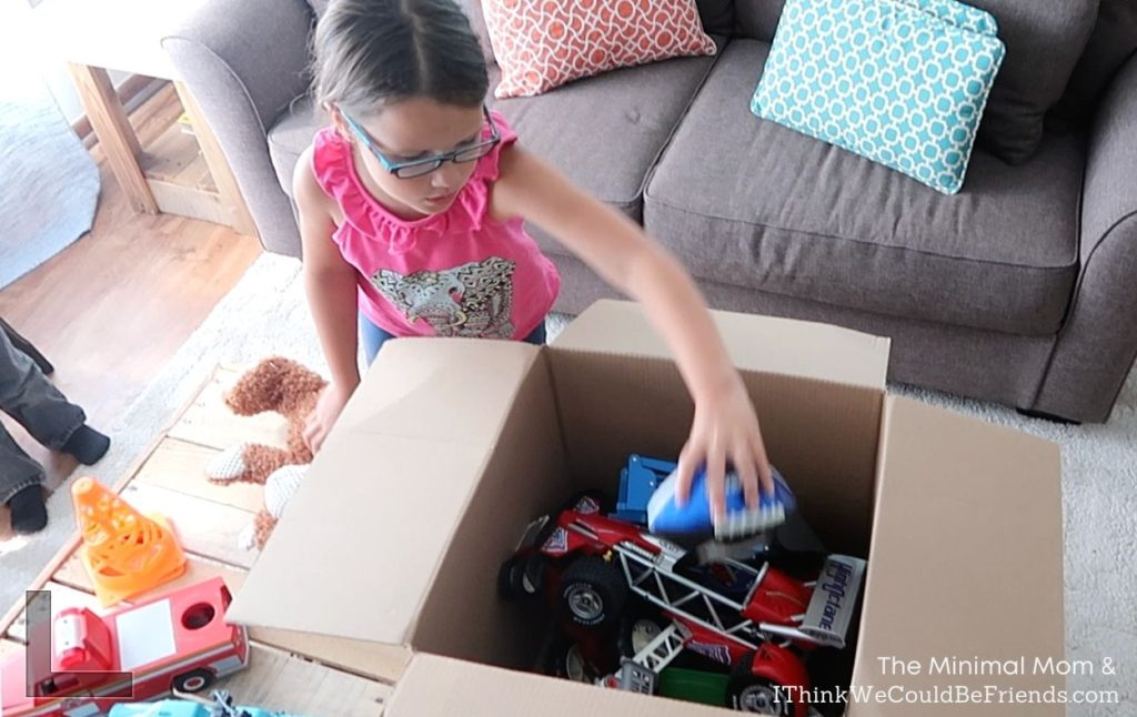 girl boxing up toys