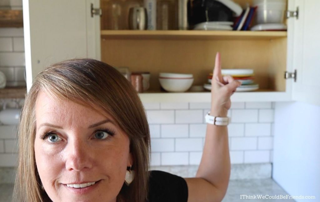 Dawn pointing to clutter in kitchen cupboards