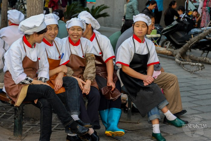 Group of women dressed in chefs clothing having a break outside their shop in Xian Muslim Qarter