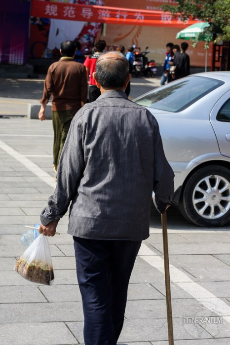 man walking with two plastic bags containing noodles