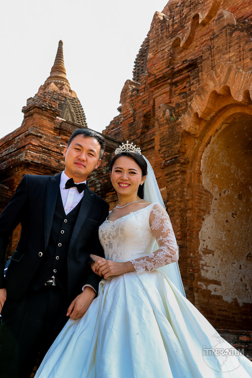 bride and groom posing against a temple in myanmar