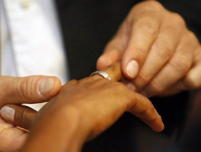 Black Man Placing Wedding Ring On Black Woman's Finger
