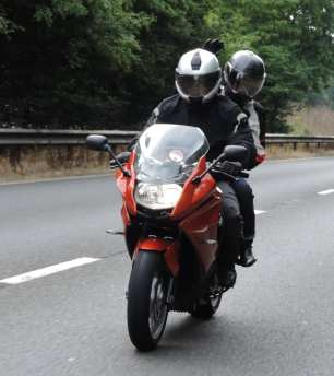 Pillion looking slightly laterally following the road