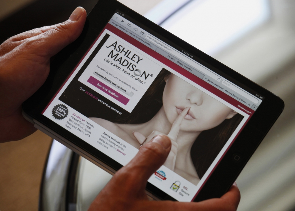 Ashley Madison founder Noel Biderman demonstrates his website on a tablet computer during an interview in Hong Kong August 28, 2013. Founded in 2002, Ashley Madison, the world's biggest online dating website for married men and women, has over 20 million users in 30 regions all over the world. REUTERS/Bobby Yip (CHINA - Tags: SOCIETY BUSINESS7 - RTX13UKU