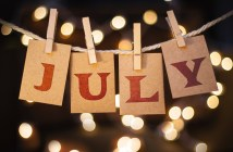 The word JULY printed on clothespin clipped cards in front of defocused glowing lights.