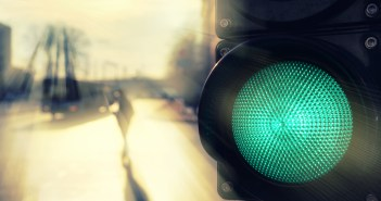 Pedestrian crossing the road in the sun at a traffic light with a green signal spring