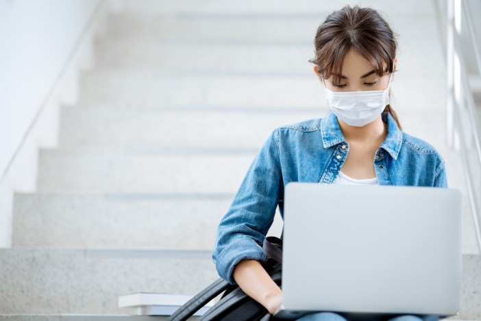 Student wearing mask working on a laptop on stairs at a university campus