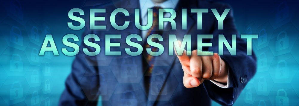 """Man in a blue suit pointing to  the words """"Security Assessment"""""""