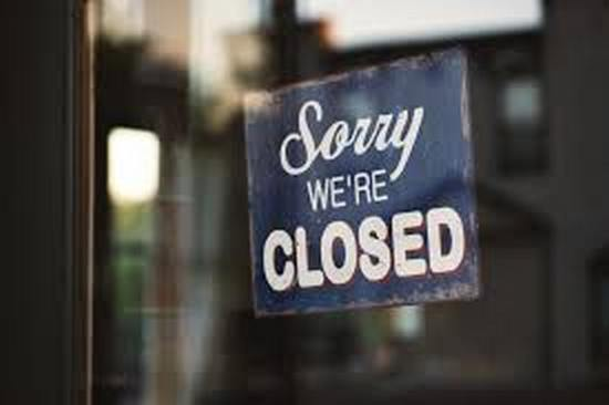 """Sorry We're Closed"" sign inthe front window of a business"