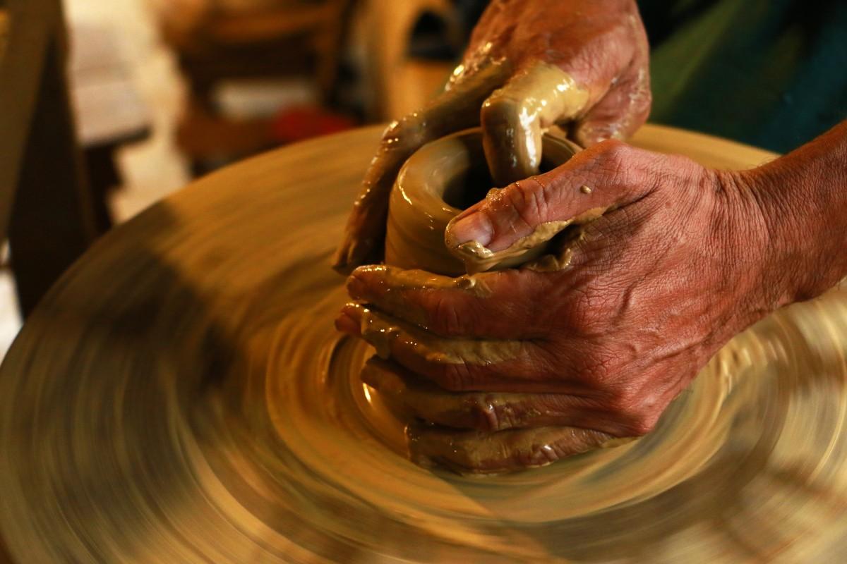 Händer som formar lera på en drejskiva