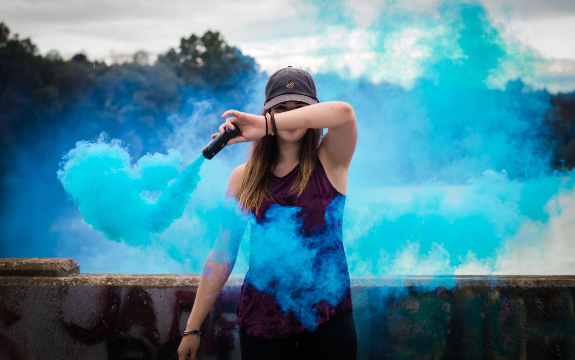 woman holding blue smoke flare