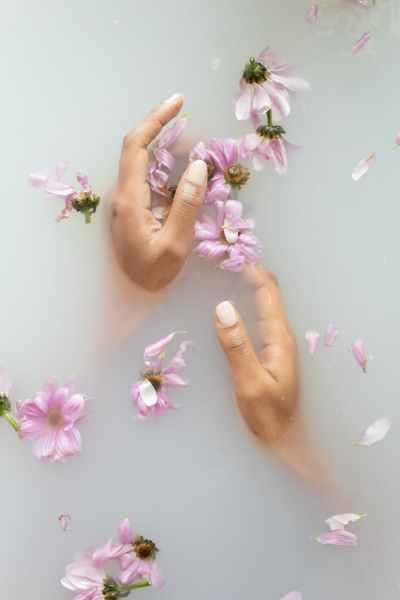 woman touching gentle flowers in water