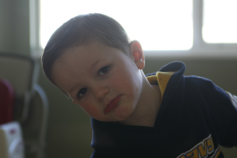 A young child facing away from a window, face looks dark
