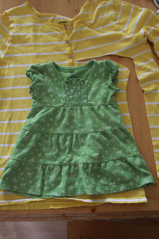 a baby dress laid over fabric to use as a pattern