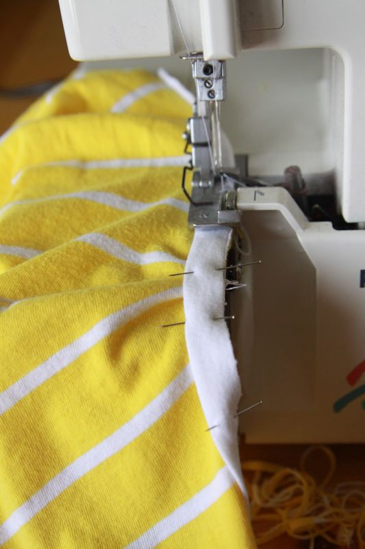 White fabric strip pinned over yellow fabric on sewing machine, yellow fabric bunched up