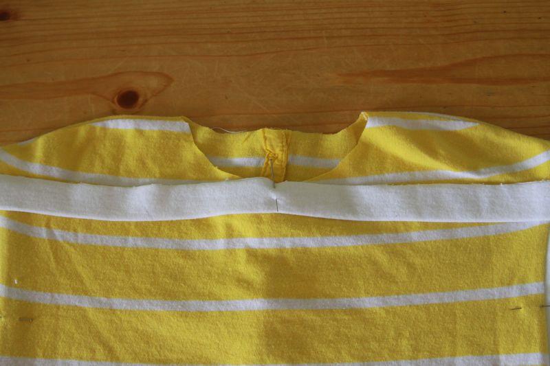 white neckbinding pinned to center neckline