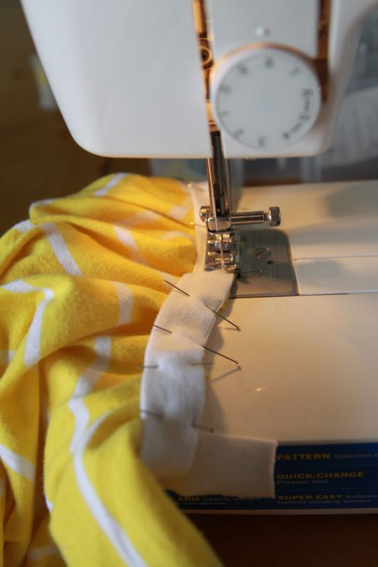 sewing binding that\'s pinned to dress, with fabric under binding bunched