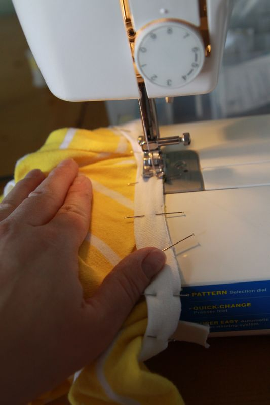 sewing binding on a sewing machine, binding stretched so fabric is flat