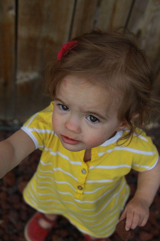A small child wearing a yellow dress