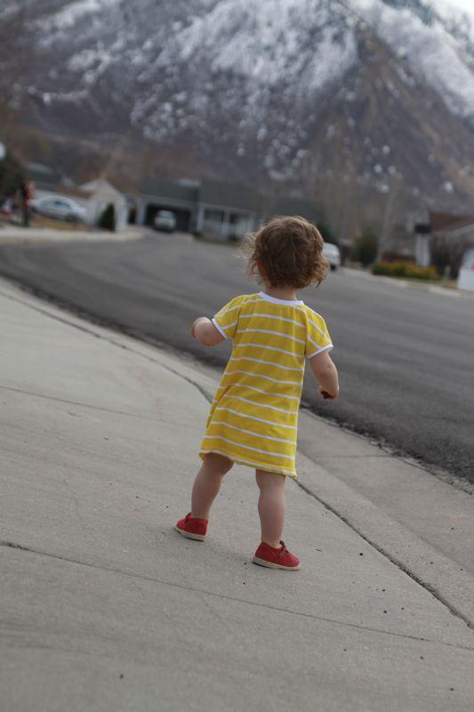 A little girl standing on a sidewalk