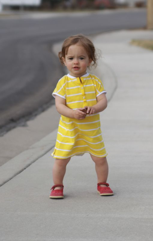 A baby girl standing on the sidewalk