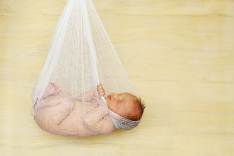 a baby in a cheesecloth cocoon in front of a wood background