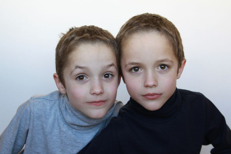 two young boys looking at the camera with white background