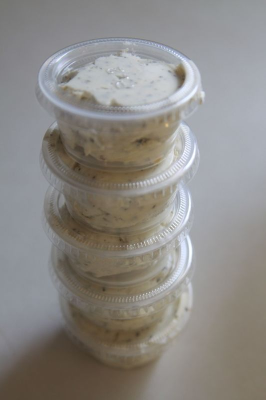 garlic herb butter spread in small plastic containers
