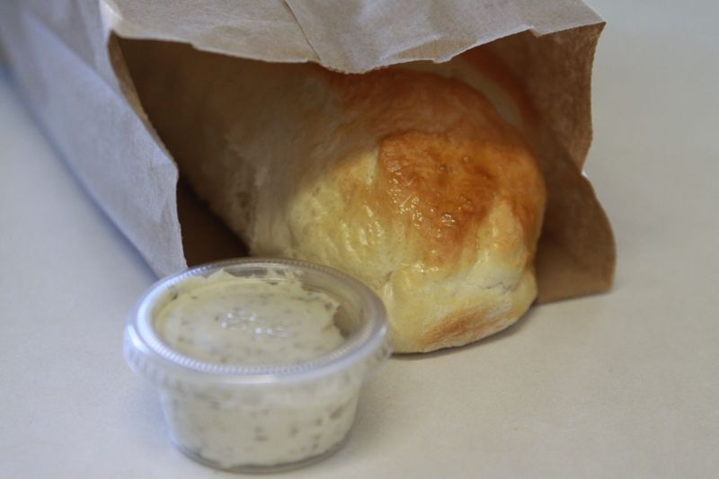A loaf of french bread in a lunch sack with plastic container of garlic spread