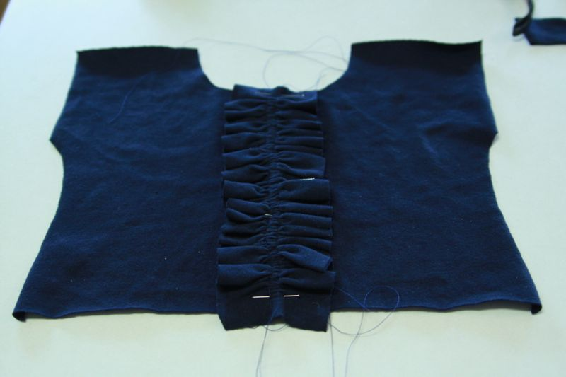 strip of fabric ruffle up with gathering stitched and pinned to center of bodice front