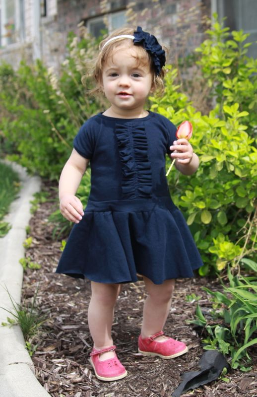 A little girl standing in a garden wearing a blue dress with a ruffle down the front and a circle skirt