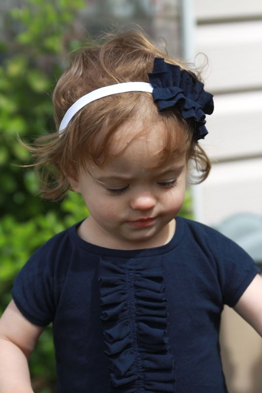 A little girl with ruffle front dress and ruffled headband