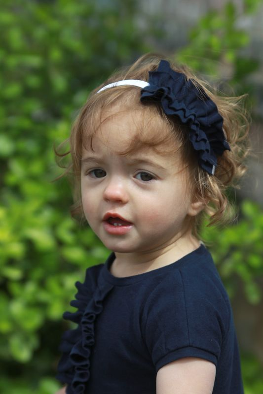 A little girl wearing a headband with ruffle on it