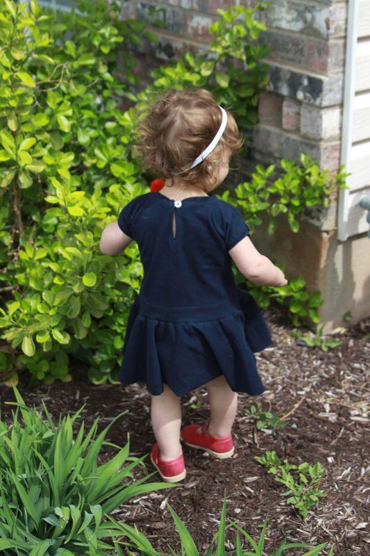 A little girl standing in a garden