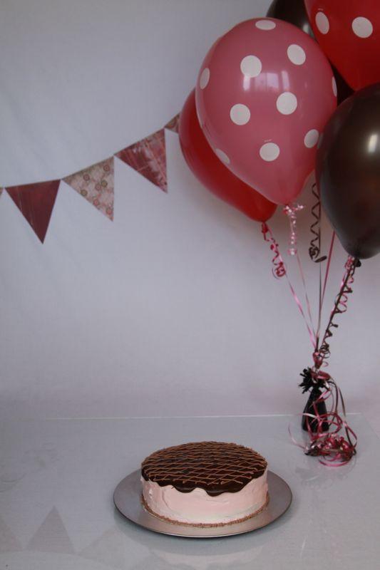 setup for cake smash photoshoot: white background, balloons, banner, cake