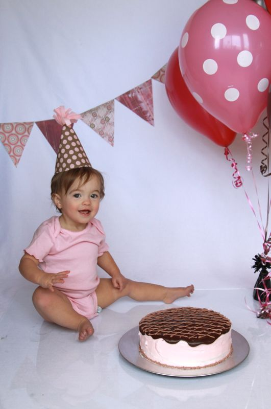 A little girl in a birthday hat by a birthday cake