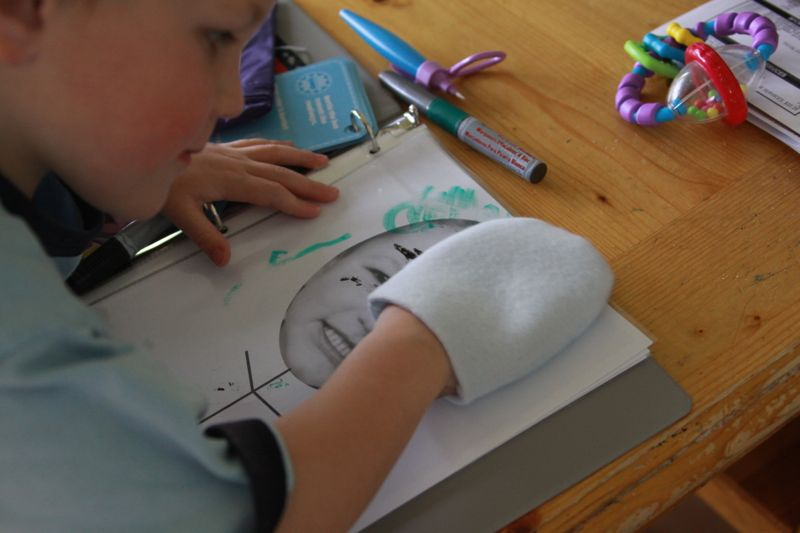 boy using fabric mitt to erase dry erase marker