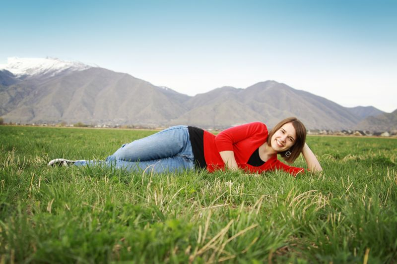 A girl lying on her side in the grass with her head on her hand