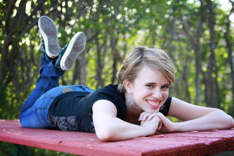 A girl lying on a picnic table with her chin on her hands and her feet kicked up behind her
