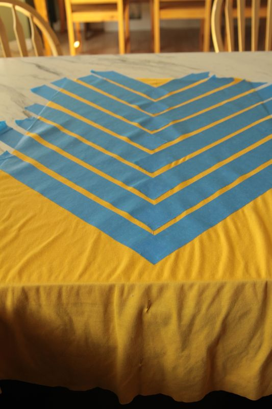 A piece of yellow fabric with painters tape on it making chevron print