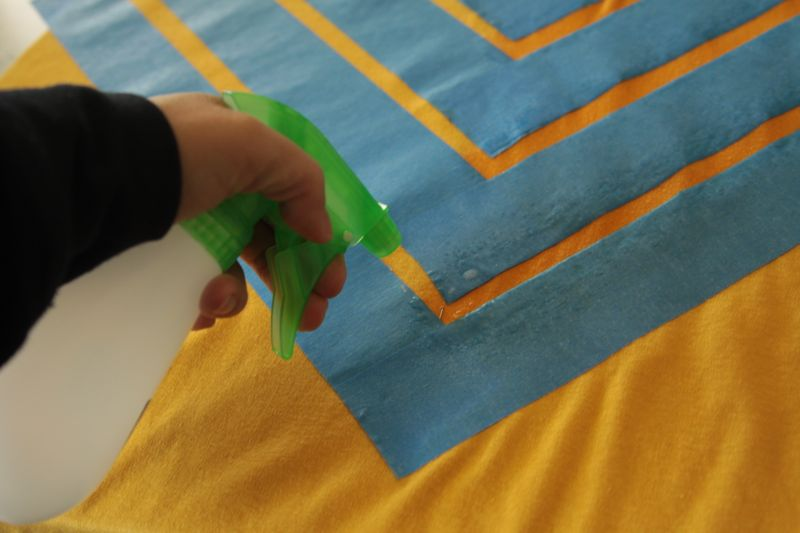 Hand holding spray bottle, spraying at fabric in between the painters tape