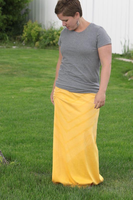 A woman wearing a grey t-shirt and yellow maxi dress