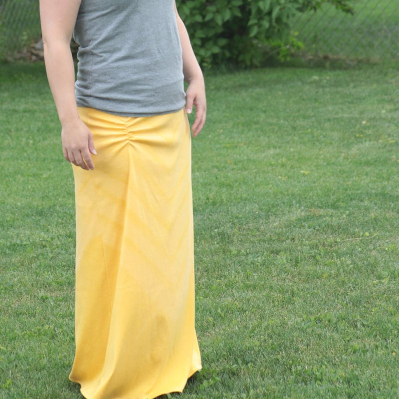 A person standing on grass wearing a yellow maxi skirt with ruching at the hip